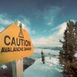 雪山に立つ危険を示す看板