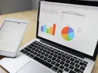 ノートパソコンとタブレット端末に表示されたデータとグラフ