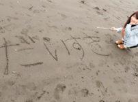 だいすきと砂浜に書いて微笑む女性