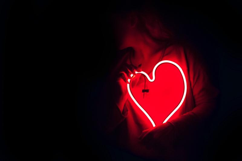 赤く光るハート型のネオンを抱きかかえる女性
