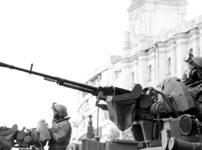 建物の前で巨大な機関砲に手をかける兵士