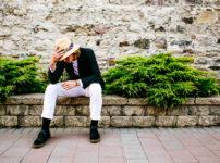 塀に座りストローハットを被る男性