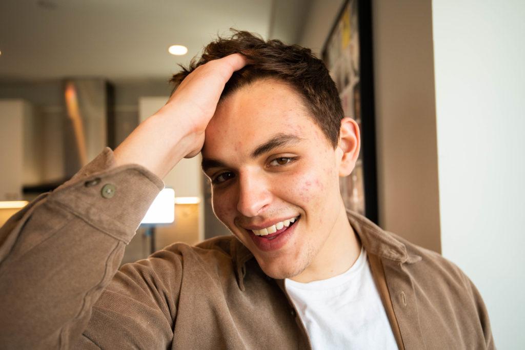 満面の笑みで髪をかき上げる男性