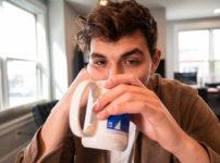 ふてくされた表情で飲み物を飲む男性