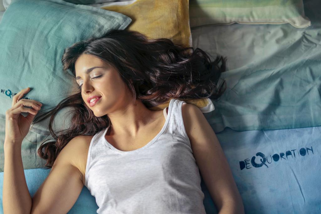 ベッドに仰向けに横たわり微笑む女性