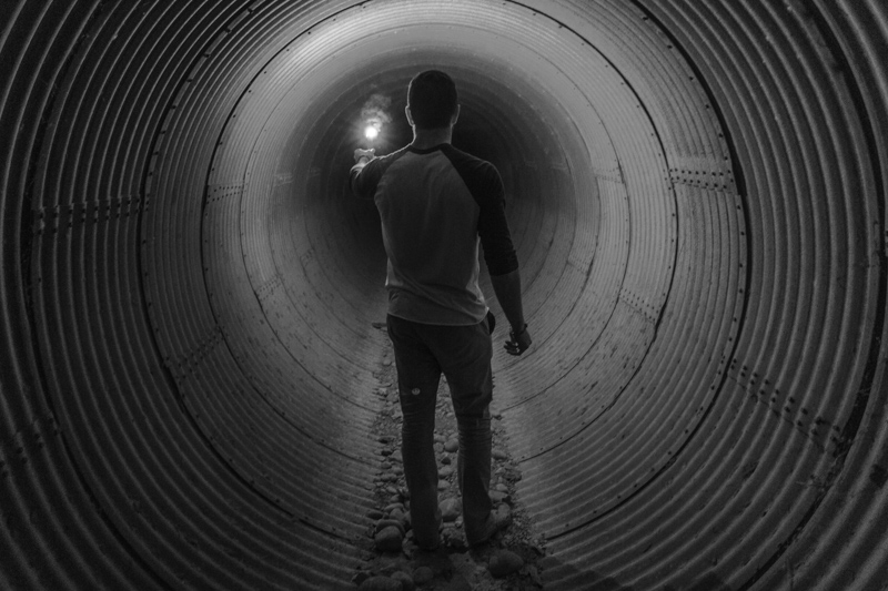 暗いトンネルであかりを灯し先を探る男性