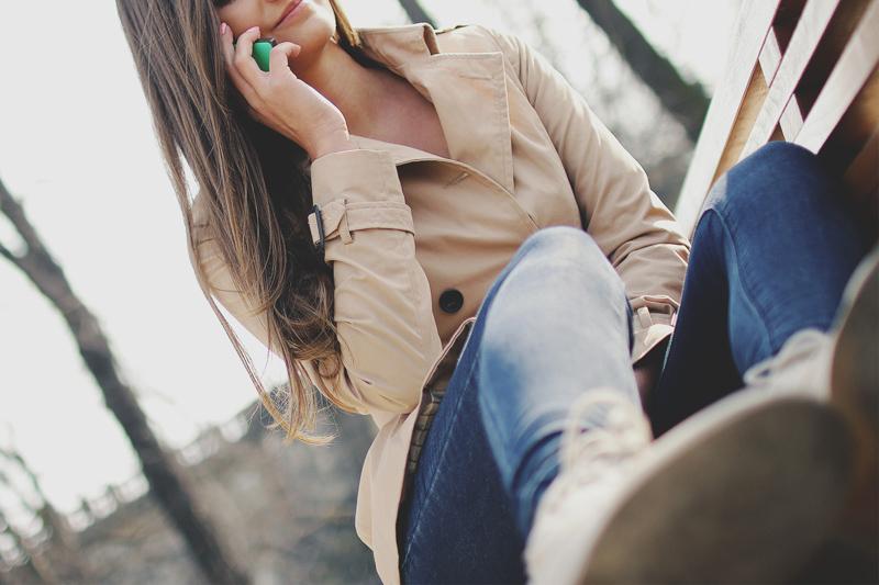 腰掛けながら笑顔で電話をする女性