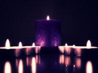暗がりの中で灯る大きな蝋燭と二手に別れて並ぶ小さな蝋燭
