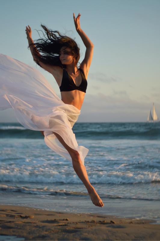 砂浜で波のように両手を大きく振り上げて飛び踊る女性