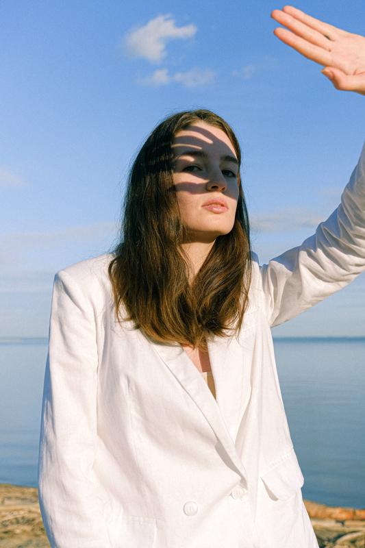 海辺で眩しそうに手をあげて夕陽を遮る女性