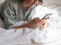 パジャマでベッドに横たわりながら両手でスマホを触る女性