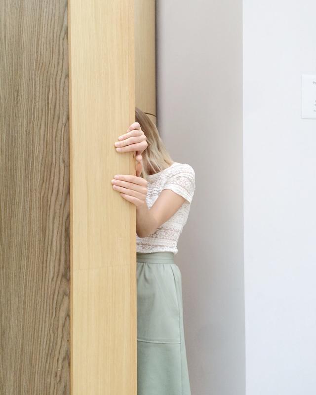 ドアの後ろに隠れる女性