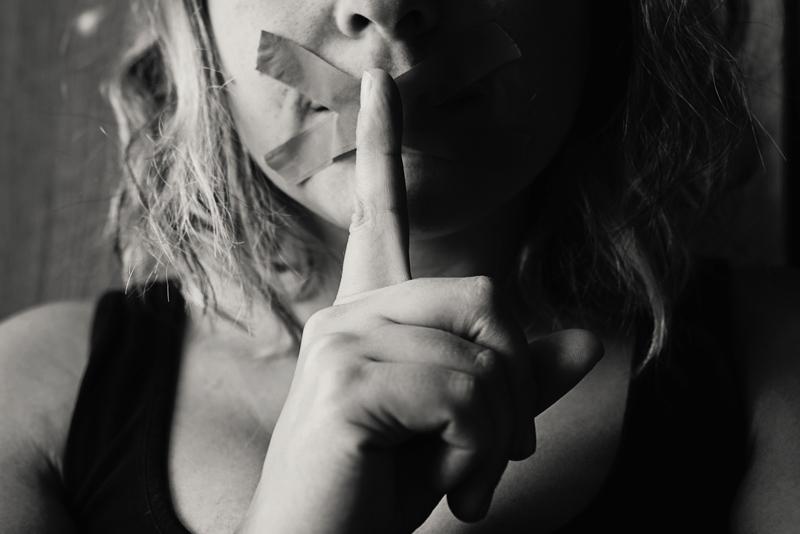 ガムテープで口を閉ざされ秘密のポーズを取る女性