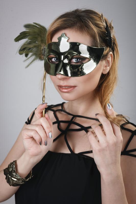 仮面を手に持ち顔につける女性