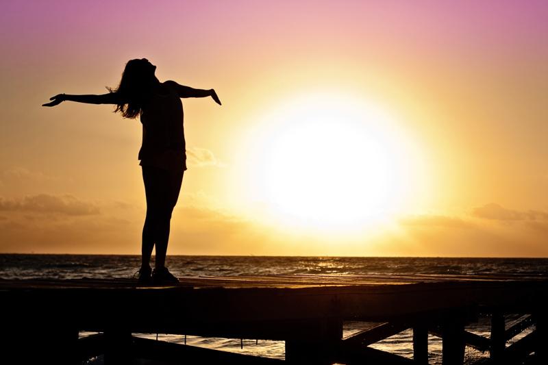 夕日が沈む海辺で大きく腕を開き天を仰ぐ女性