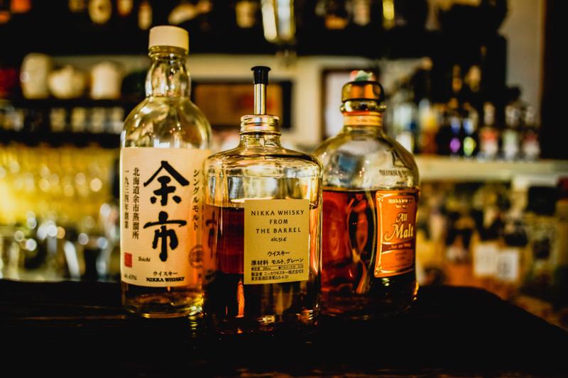 3つのウィスキーの瓶が置かれたバーカウンター