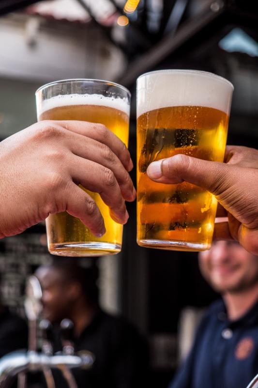 ビールが注がれたグラスを持ち乾杯する人々